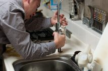 Un plombier qui répare un robinet